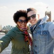 Happy teenage couple taking selfie in london city — Stock Photo #78624242