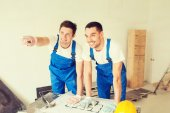 Smiling builders with blueprint — Stock Photo