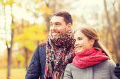 Smiling couple hugging on bridge in autumn park — Stock Photo