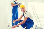 Builders with tablet pc and equipment indoors — Stock Photo