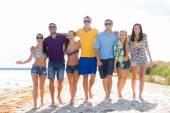 Mutlu arkadaşlar kumsal boyunca yürüyüş grup — Stok fotoğraf