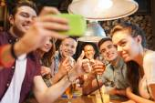 Happy friends with smartphone taking selfie at bar — Stock Photo
