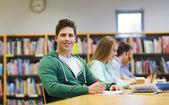 Student szczęśliwy chłopiec czytanie książek w bibliotece — Zdjęcie stockowe