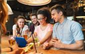 Happy friends with tablet pc and drinks at bar — Stock Photo