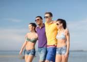 Group of happy friends walking along beach — Stock Photo