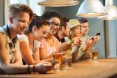 Happy friends with smartphones and drinks at bar — Stock Photo