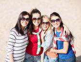 Happy teenage girls or young women on beach — Stock Photo
