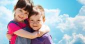 Two happy kids hugging over blue sky and clouds — Stock Photo