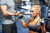 Mężczyzna i kobieta wyginanie mięśni na siłowni maszyna — Zdjęcie stockowe