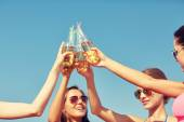 Close up of happy young women clinking bottles — Stock Photo