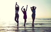 Happy female friends dancing on beach — Stock Photo