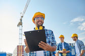 Builder in hardhat with clipboard at construction — Stock Photo