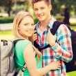Smiling couple with backpacks in nature — Stock Photo #79027290
