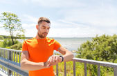 Young man with smart wristwatch at seaside — Stock Photo