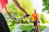 Close up of happy couple riding bicycle outdoors — Stock Photo