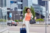 Happy woman with travel bag calling on smartphone — Stock Photo