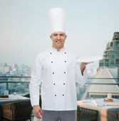 Happy male chef cook showing empty plate — Stock Photo