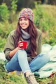 Smiling young woman with cup sitting in camping — Stock Photo