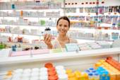 Happy female customer with drug jar at pharmacy — Stock Photo