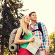 Smiling couple with map and backpack in nature — Stock Photo #79066098