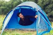 Smiling male tourist with beard in tent — Stock Photo