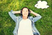 Smiling young girl in headphones lying on grass — Stock Photo