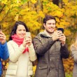 Smiling friends with smartphones in city park — Stock Photo #79248848