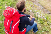 Man hiker with red backpack sitting on ground — Stock Photo