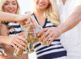 Close up of friends clinking bottles with drinks — Stock Photo