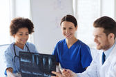 Group of happy doctors discussing x-ray image — Stock Photo