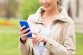 Close up of woman calling on smartphone in park — Stock Photo