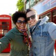 Happy teenage couple taking selfie in london city — 图库照片 #79384458