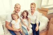 S úsměvem rodiče a dvě malé holčičky v novém domově — Stock fotografie