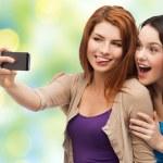 Happy teenage girls taking selfie with smartphone — Stock Photo #79481180
