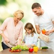 Happy family cooking vegetable salad for dinner — Stock Photo #79482944