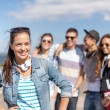 Teenage girl with headphones and friends outside — Stock Photo #79486330