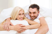 Happy couple in bed at home — Stock Photo