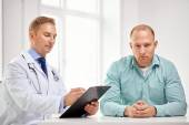 Male doctor and patient with clipboard at hospital — Stock Photo