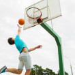 Young man playing basketball outdoors — Stock Photo #79937994