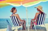 Happy women sunbathing in lounges on beach — Stock Photo