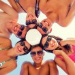 Smiling friends in circle on summer beach — Stock Photo #80042320