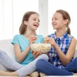 Happy girls with popcorn watching tv at home — Stock Photo #80045596