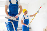 Two builders with painting tools repairing room — Stock Photo