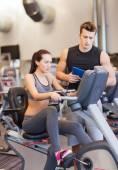 Kvinna med tränare på motionscykel i gym — Stockfoto