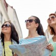 Smiling teenage girls with map and camera outdoors — Stock Photo #80122014