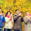Smiling friends with smartphones in city park — Stock Photo #80474198
