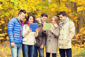 Group of smiling friends with tablets in park — Stock Photo