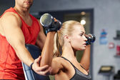 Man and woman with dumbbells in gym — Stock Photo