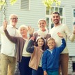 Happy family waving hands in front of house — Stock Photo #80612554