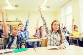 Group of school kids raising hands in classroom — Stock Photo
